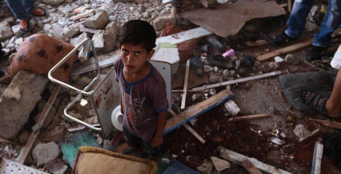 Un bambino tra le macerie della scuola delle Nazioni Unite colpita dall'artiglieria israeliana - Mohammed Saber 30 luglio, Jabaliya, Palestina © ANSA