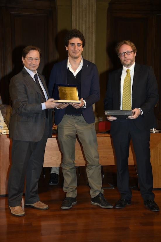 Il vice presidente del Gruppo Cronisti lombardi Antonello Capone ed il consigliere Fabrizio Cassinelli consegnano il premio a Paolo Maggioni (RaiNews24)